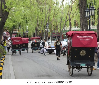 BEIJING-CHINA-.21 April. Tourists in a rickshaw. Though, they became a very popular tourist transport they are banned in many cities as a cause of traffic jam. Beijing, 21 April.2015.