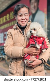 BEIJING-DEC. 19, 2008. Chinese woman with her pet. Once banned by Mao Zedong as bourgeois, having a pet became a symbol of economic progress in China, pet sector grows to 15.8 billion yuan by 2019.