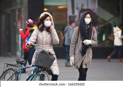 BEIJING-DEC 8: People with face masks are seen on Dec 8,2013 in Beijing, China.  104 cities in China suffered from severe air pollution on Dec7, Beijing was among that hit the hardest