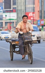 BEIJING-JULY 10, 2015. Man on rusty three wheeled freight bike. Although municipal governments try to ban them out this transportation mode is still convenient in dense, congested Chinese cities.