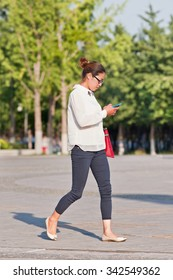 BEIJING-JULY 3, 2015. Fashionable attractive young woman with smartphone. China has currently 519.7 million smartphone users. That figure will rise to 574.2 million Chinese smartphone users by 2015.