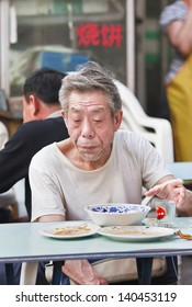 BEIJING-MAY 21. Old Chinese man eats outside. China's elderly surpasses 200 million in 2014, top 300 million by 2025. By 2042, more than 30% of China's population ages over 60. Beijing, May 21, 2008.