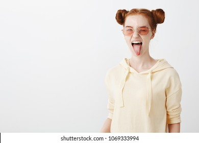 Being up to all trends in fashion industry. Portrait of cool attractive redhead girl with trendy haircut and sunglasses winking, showing tongue, being sassy while trying to make impression on party