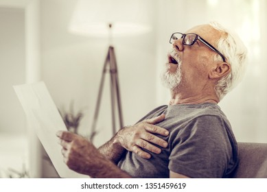 Being amazed at papers. Portrait of shocked aged grey-haired attractive man in glasses being amazed at medical papers in hands