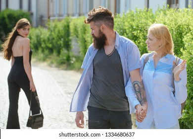 Being a bit of a womaniser. Hipster choosing between two women. Love triangle and threesome. Man cheating his girlfriend. Bearded man looking at other girl. Betrayal and infidelity. Unfaithful love.