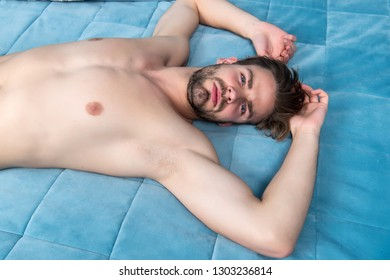 Being calm and relaxed. Single man after waking up in morning. Awake for morning routine. Relaxing man in bedroom. Sexy man lying in bed at home. Feeling alone and tired.