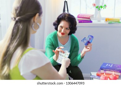 Being deceived. Cheerful sly woman taking the money while deceiving her client