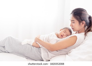 Being mom is so exhausted.  Tired mother laid in bed with newborn baby at night. Authentic real life exhausted parent taking rest with newborn child.