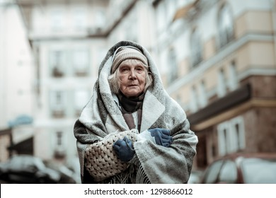 Being an outcast. Depressed aged woman having a difficult life while being an outcast