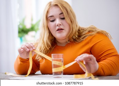 Being overweight. Concentrated overweight woman sitting at her table and holding a measuring tape