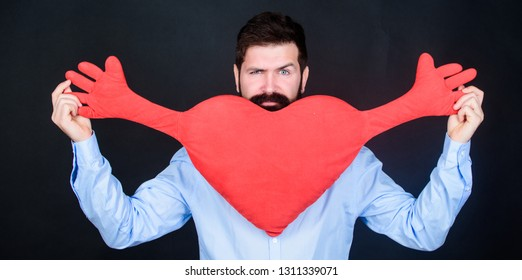 Being utterly romantically lovestruck. Having heart attack and heartache. Unhealthy man holding big red heart. Valentines man expressing love on 14 february. Love sickness and heart problems.