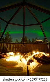 """Being witnessed the nature great show """"Aurora Borealis"""" on warm bed inside the glass Igloo in Lapland, Finland."""