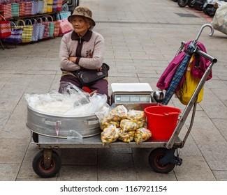 Beipu, Hsinchu County, Taiwan - December 26 2015: An elderly street vendor selling fruits