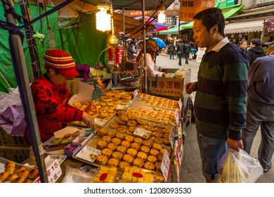Beipu, Hsinchu County, Taiwan - December 26 2015: An elderly street vendor selling traditional cookies at the Beipu market