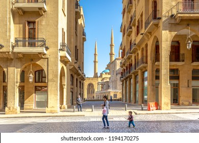 Beirut, Lebanon - Feb 5th 2018 - Young mother and a kid walking in the old town of Beirut, mosque in the background, blue sky, Beirut, Lebanon
