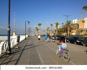 Beirut, Lebanon - June 19, 2015: People're walking via Beirut's famous seaside promenade and one girl's biking in sunny day with the sea lantern at the background.