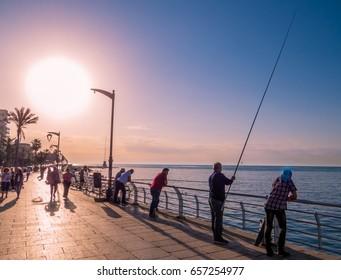 BEIRUT, LEBANON - MAY 22, 2017: People fishing at sunset on the seafront Corniche promenade.