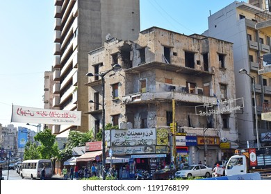 BEIRUT, LEBANON - OCTOBER 1, 2017: Traces of past civil war on the streets of Beirut. Damaged building among the signboards.