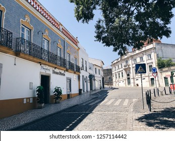 "Beja, Portugal - August 12, 2018: Small Portugese town street view. Empty Sunday street. Building of the hotel ""Dona Maria""."