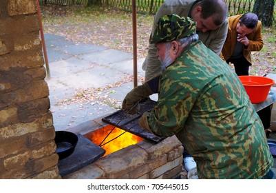 Belarus, Bobruisk district, Glusha village, October 3, 2015: Potter, old ceramic oven and baking the product