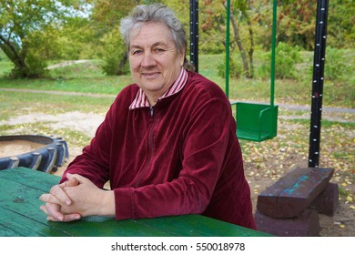 Belarus, Bobruisk district, the village of Slobodka, September 15, 2015: A smiling woman sitting at a wooden table in a park with her hands folded on the table