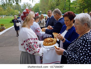 Belarus, Bobruisk district, the village of Slobodka, September 25, 2015: Women in national costumes hold a loaf. Guests taste pieces of baking.