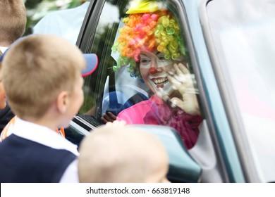 Belarus, the city of Gomel,May 24, 2017,Zyabrovsky kindergarten, graduation day.The clown looks through the glass of the car for joyful children