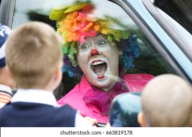 Belarus, the city of Gomel,May 24, 2017,Zyabrovsky kindergarten, graduation day.The clown looks through the glass of the car for joyful children.Cheer children