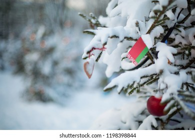 Belarus flag. Christmas background outdoor. Christmas tree covered with snow and decorations and Belorussian flag. Christmas holiday greeting card.