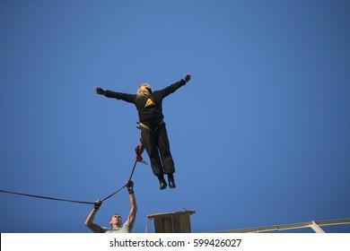 Belarus, Gomel, 10.03.2017 year Jumping from the bridge with a rope. RoupeJumping Woman jumping from the bridge.