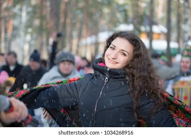 Belarus, Gomel, February 18, 2018. Russian holiday seeing off winter Maslenitsa.Beautiful brown-eyed brunette in Russian scarf in winter forest dancing