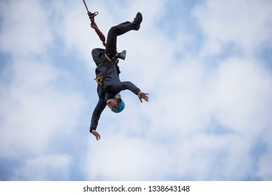 Belarus, Gomel, March 08, 2019. Jumping from the bridge to the rope.Ropejumping.A man jumps from a great height and flies upside down in the sky on a rope. Extreme passion