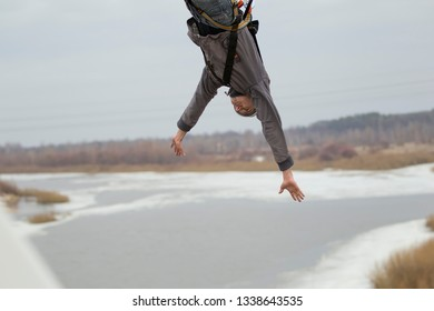 Belarus, Gomel, March 08, 2019. Jumping from the bridge to the rope.Ropejumping.A man jumps from a great height and flies in the sky on a rope above the river. Extreme passion
