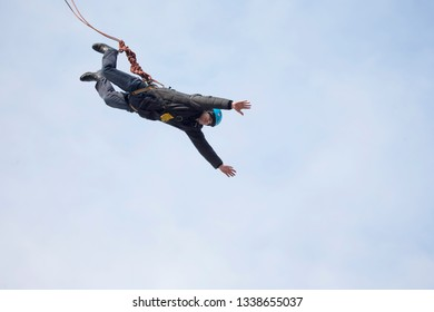 Belarus, Gomel, March 08, 2019. Jumping from the bridge to the rope.Ropejumping.A man jumps from a great height and flies down in the sky on a rope. Extreme passion