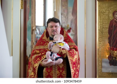 Belarus, Gomel, May 6, 2018. Church of Volotovo. Baptism of a newborn child.The priest carries the child in his arms.Carry a boy through purgatory