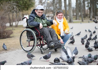 Belarus, Gomel, on April 11, 2018. City Day. Central Park.A man in a wheelchair with his wife is feeding pigeons