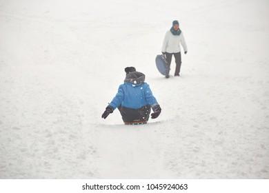 Belarus, Grodno, Lake Molochnoe in the winter. People sledding on the slides
