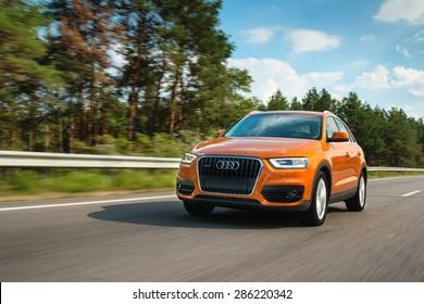 Belarus, highway, September  1 - 2013: orange Audi Q3 in motion on highway at summer noon