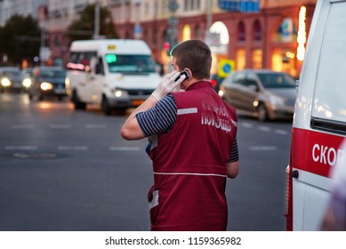 Belarus, Minsk - 17 Aug 2018. Paramedic of an ambulance brigade attending an emergency call in the streets of the city calls the dispatcher by cell phone. Worker of emergency medical services.