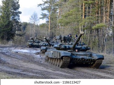 Belarus, Minsk 28.04.2016: Russian armored combat vehicles are navigating through marshland through forests. Tankmen on the T-90 tanks of the Russian army. Joint Exercises