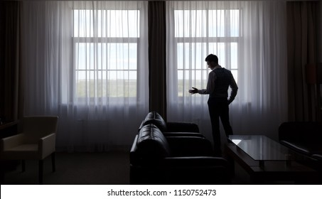 Belarus, Minsk - June 03 2018: Back view of man standing and looking out a large window at Victoria Olympus hotel and business center. The groom expects the bride in the hotel room.