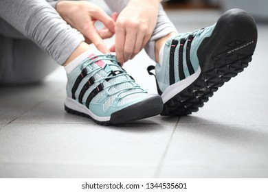 Belarus, Minsk, March 18, 2012. The girl in sneakers Adidas terrex sits on the floor of a fitness center.