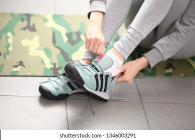 Belarus, Minsk, March 18, 2012. The girl in sneakers Adidas terrex sits on the floor of a fitness center tying shoelaces