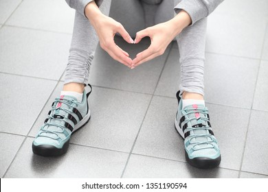 Belarus, Minsk, March 18, 2012. The girl in sneakers Adidas terrex sits on the floor of a fitness center