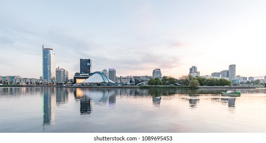 Belarus, Minsk - May 02, 2018. Embankment of the Svisloch River. Panorama of the city center at sunset. Sports buildings, business centers and hotels.