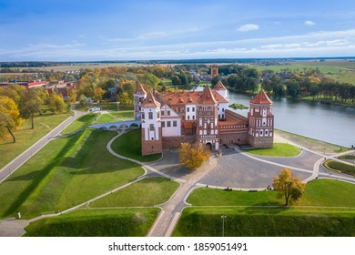 Belarus. Mir castle in the Minsk region. Aerial view of a medieval castle on a bright sunny autumn day. Old architecture in colorful park view from above. - Shutterstock ID 1859051491