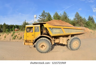 Belarus, Radoshkovichi quarry. 07.20.2018:Serious Russian man driving a big yellow mining truck. Tipper. Belaz. Career. Supersize car. Transportation of sand on a sandy road. Industrial landscape