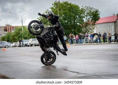 Belarus-07.06.2019: Moto rider making a stunt on his motorbike. Biker doing a difficult and dangerous stunt.