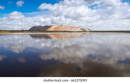 Belarus,Soligorsk. Extraction And Mining Potassium Salt. Industrial Landscape With Large Excavator Machine ( Dragline ),Huge Mountains Of Waste Ore After  Extraction Of Potassium And Blue Cloudy Sky