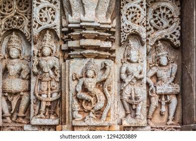 Belavadi, Karnataka, India - November 2, 2013: Veera Narayana Temple. Closeup of outside wall panel with nobility, dancing girl and musicians. All face taken off by Islamic conquerors.
